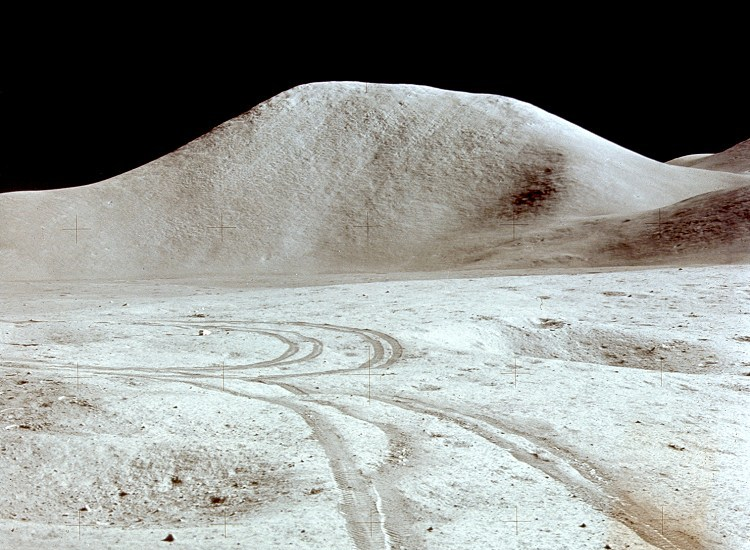 All the mountains on the Moon are rounded like Mt. Hadley (from Apollo 15) because they are buried under fallout kicked up by eons of impacts. Astronauts reported the upper layer of dust was as fine as flour and slippery enough to ski on. NASA image.